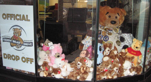 a pile of teddy bears in a window