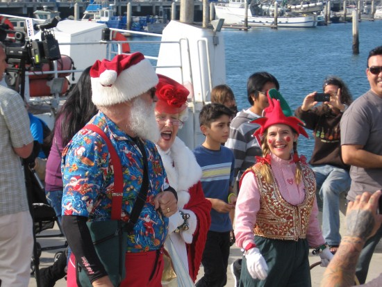 surfing santa walks down the pier for his reception
