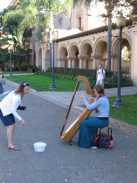 Lady plays harp on El Prado in Balboa Park.
