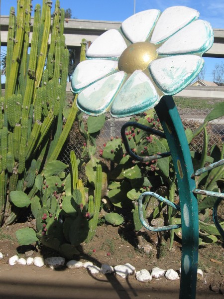 Flower sculpture and cacti beside freeway.