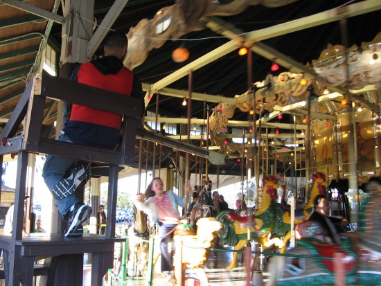 Girl tries to grab brass ring on Balboa Park carousel.