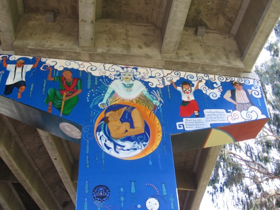 05 Figures in diverse costumes beneath a concrete jungle.