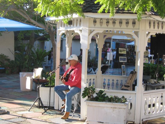 Man plays guitar in Spanish Village gazebo.