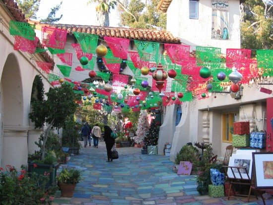 Santa awaits beyond colorful decorations in Spanish Village.