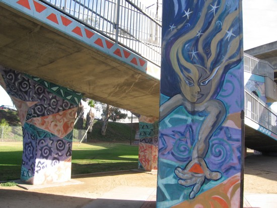 Small mural near pedestrian walkway that crosses freeway.