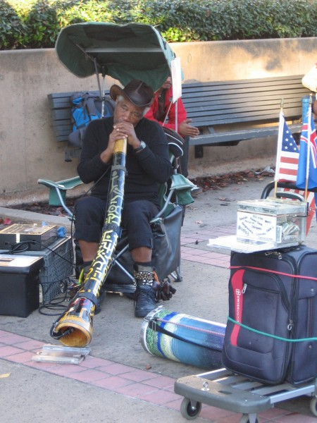 Street performer plays an Australian didgeridoo.