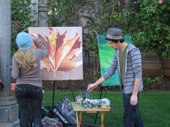 Two artists on El Prado paint colorful canvases.