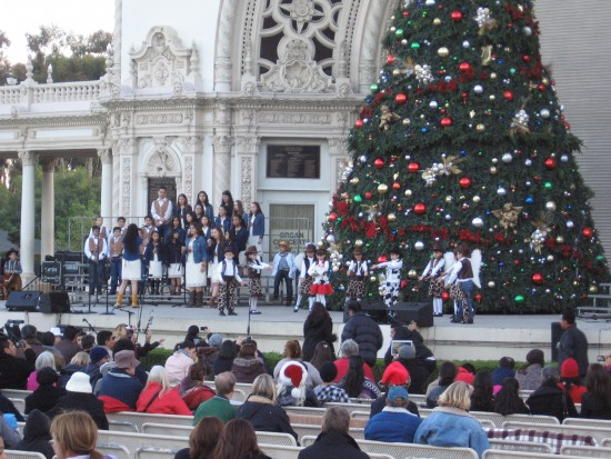 Children perform in front of big Christmas tree on Spreckels Organ Pavilion stage.