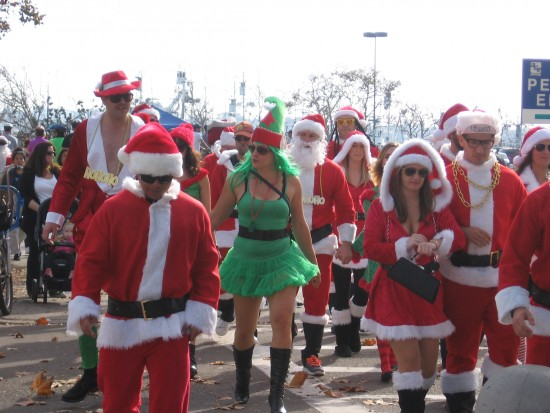 A mob of Santas and one green elf.