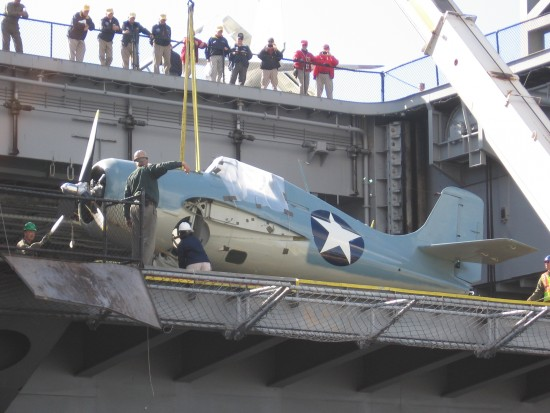 Aircraft is placed on USS Midway while people watch from flight deck.