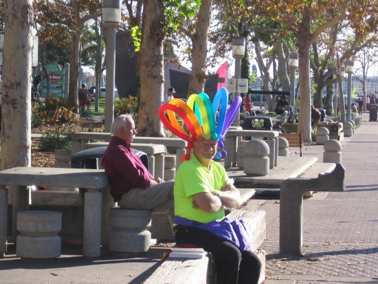 Balloon twister guy sits patiently on the Embarcadero.
