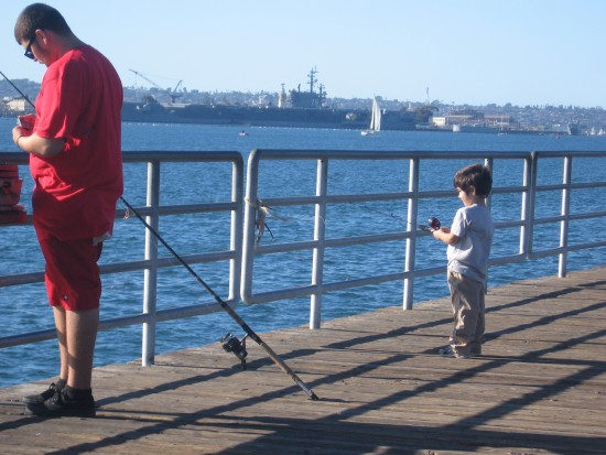 Boy fishes with dad on Embarcadero Marina Park South pier.