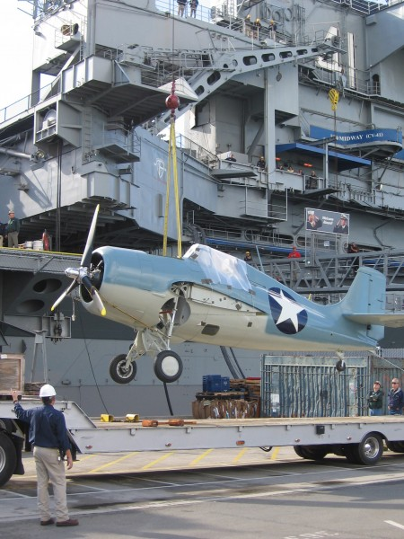 Crane begins to lift F4F Wildcat onto USS Midway.