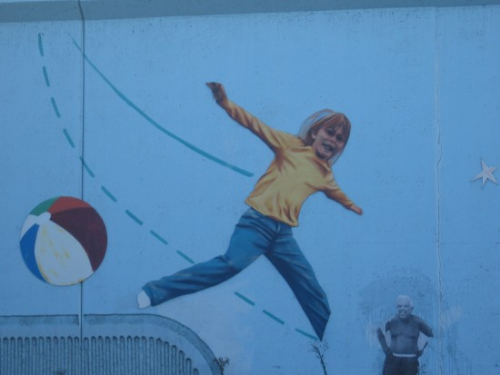 Flying with arms wide across a lively public mural.