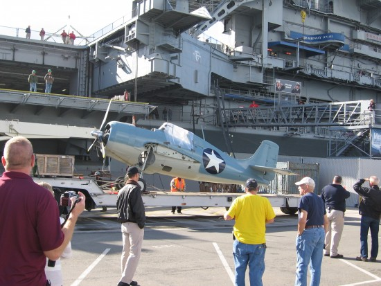 Historic airplane transported by truck to USS Midway.
