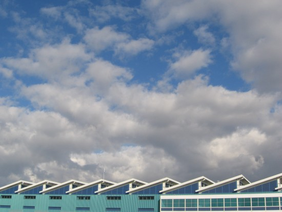 Roof of Broadway Pier Port Pavilion and clouds in blue sky.