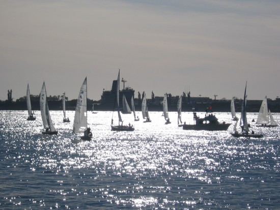 Sailboats race in a bright silvery space.