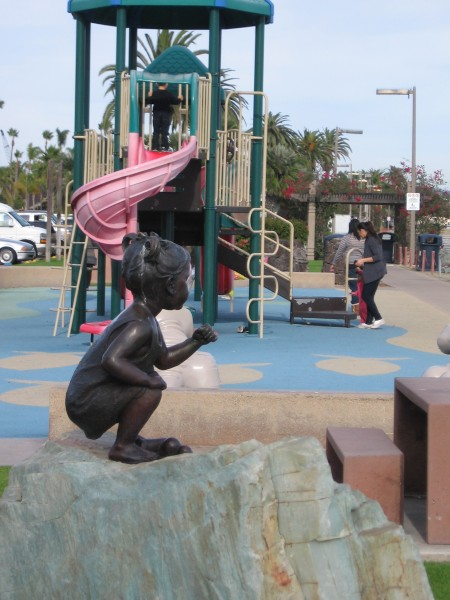 Sculpture of toddler on rock near Shelter Island playground.