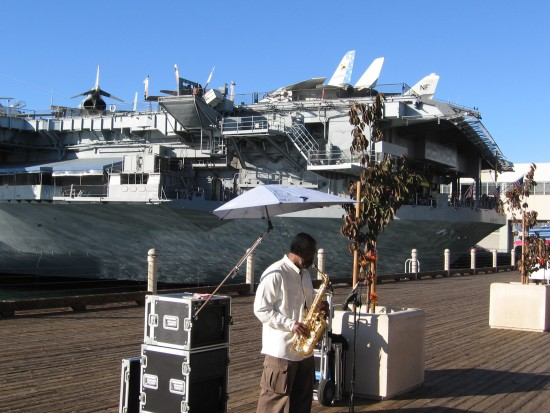 Street performer plays sax by the USS Midway.