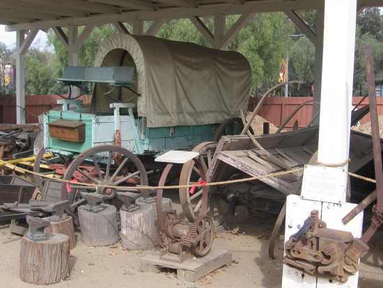 Covered wagon, anvils and relics of the Old West behind Seeley Stable.