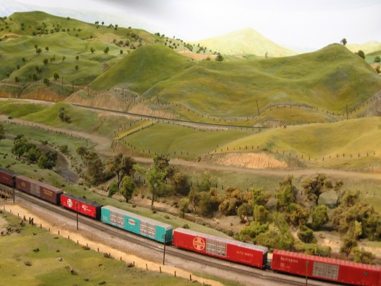 HO Scale model train travels through Tehachapi Pass exhibit.