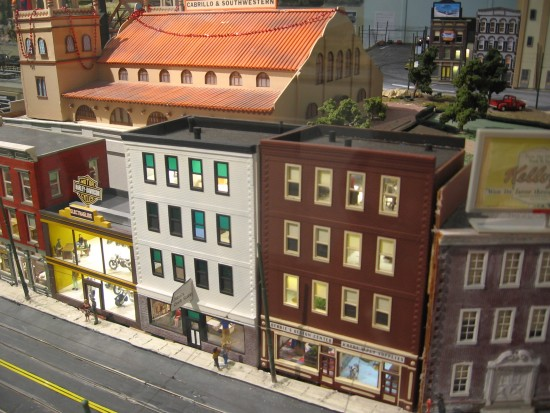 Large O Scale model train exhibit includes many detailed buildings.