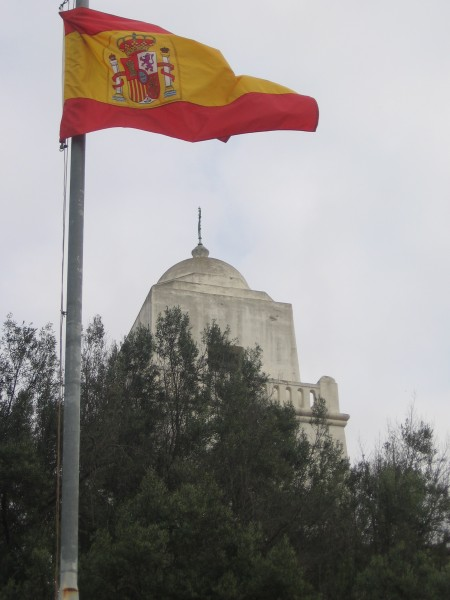 The old presidio rises beyond billowing Spanish flag.