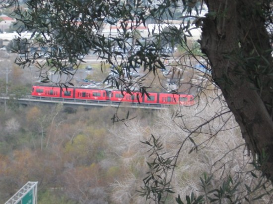 Looking down at a red trolley in Mission Valley.