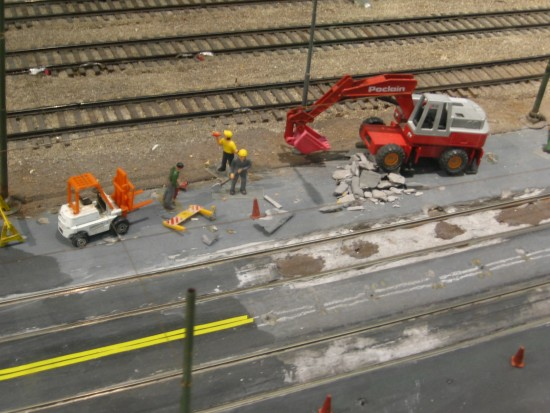 Tiny human figures at work near some trolley tracks.