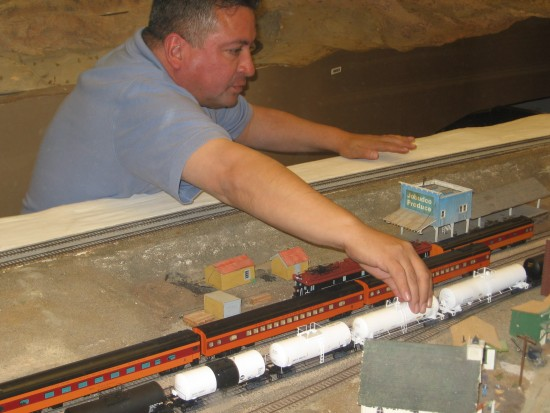 Member of Model Railroad Museum attends to derailed train.
