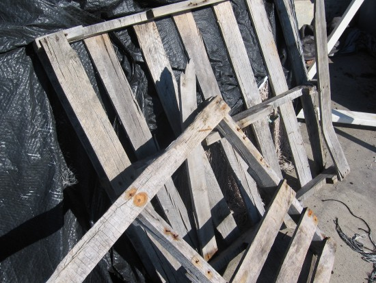 Broken pallets lean against mound of nets covered in plastic.