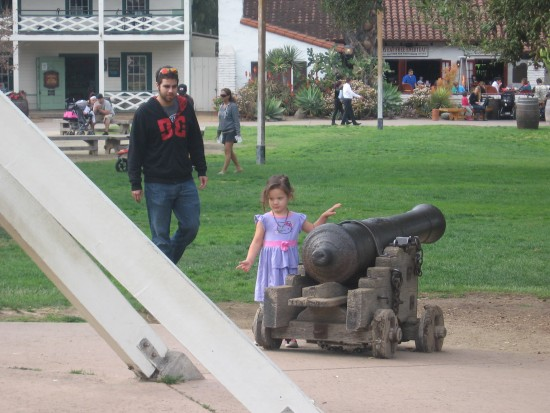 Girl walks past cannon in Old Town San Diego State Historic Park.