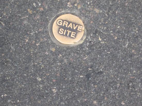 Grave site marker embedded in San Diego Avenue asphalt.