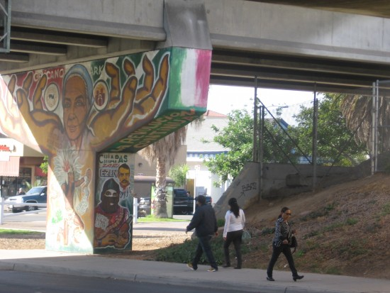 Pedestrians near Chicano Park walk past public art.