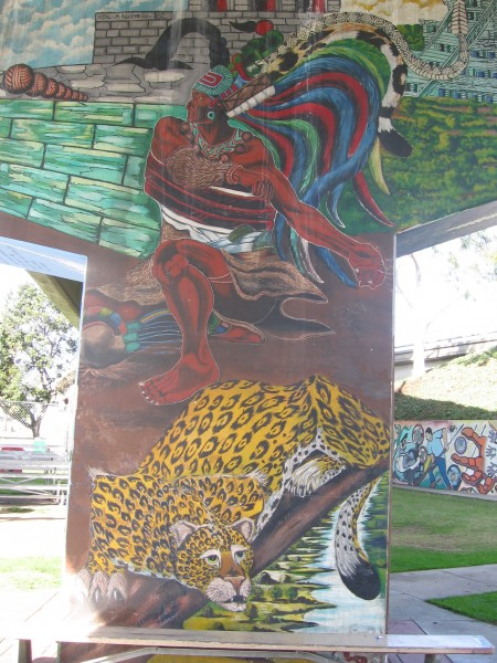 Painted jaguar crouches near basketball court.