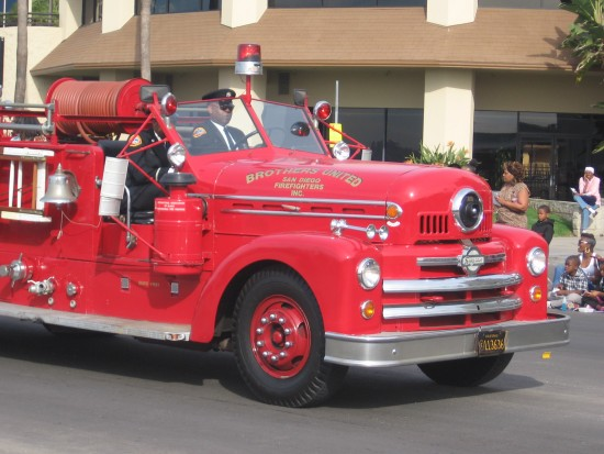 A vintage fire truck rolls down Harbor Drive.