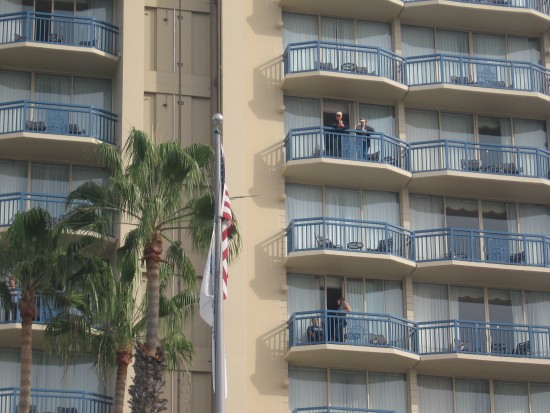 People watch parade from hotel balconies across the street.