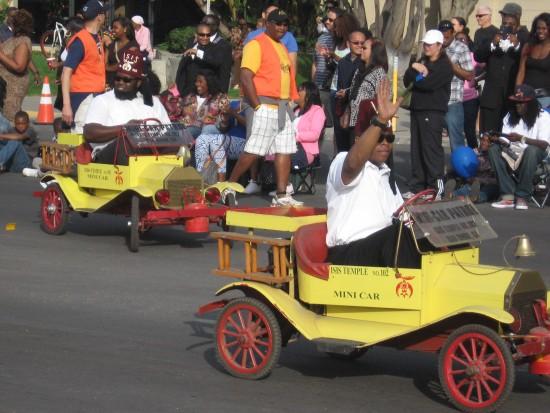Some guys having fun in yellow mini cars.
