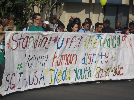 Banner holders stand up for human dignity.