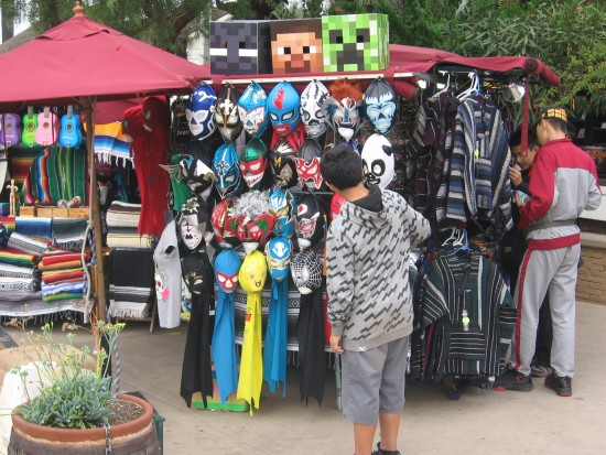 Kid checks out a bunch of Mexican Lucha Libre masks.