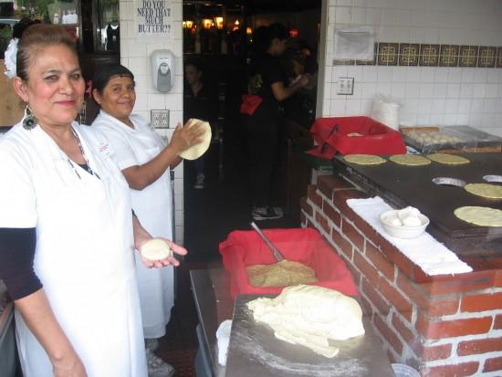 Ladies prepare fresh tortillas for people passing on the sidewalk.
