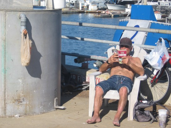 Man reads book on Tuna Harbor Pier on New Year's Day.