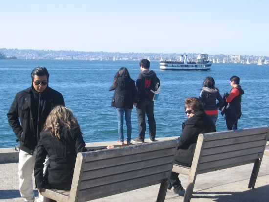 People gaze at San Diego Bay from benches by The Fish Market.