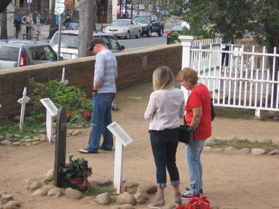 People read plaques and headstones in Old Town cemetery.