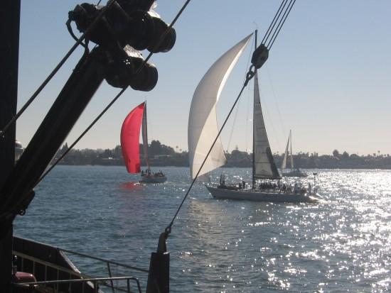 Sailboats pass live bait fishing boat docked at Tuna Harbor Pier.