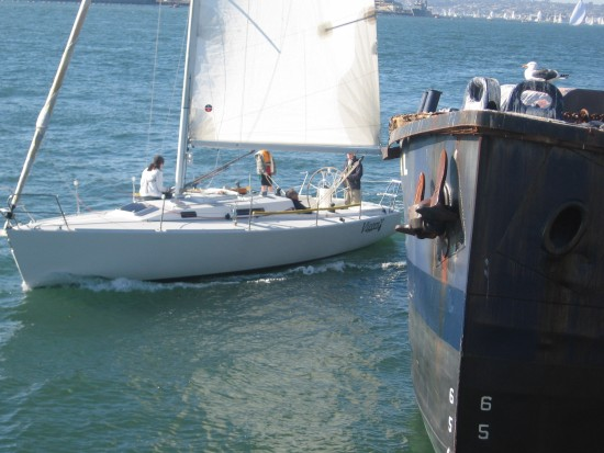 Small sailboat passes live bait boat on San Diego Bay.