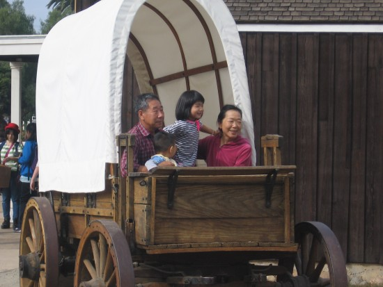 Tourists pose for a picture in an old covered wagon in Old Town.