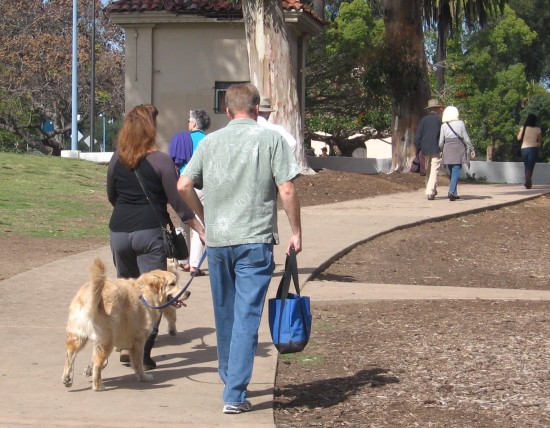 Dogs and humans head toward Bark in Balboa Park.