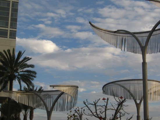 Clouds above metal trees in front of Hilton hotel.