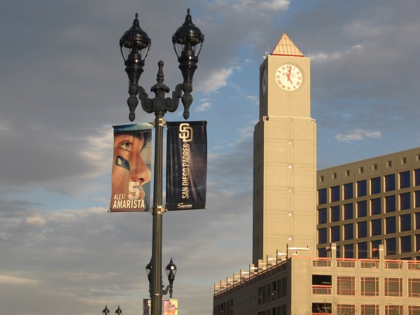 Imperial Transit Station clock tower and Padres banner under clouds.
